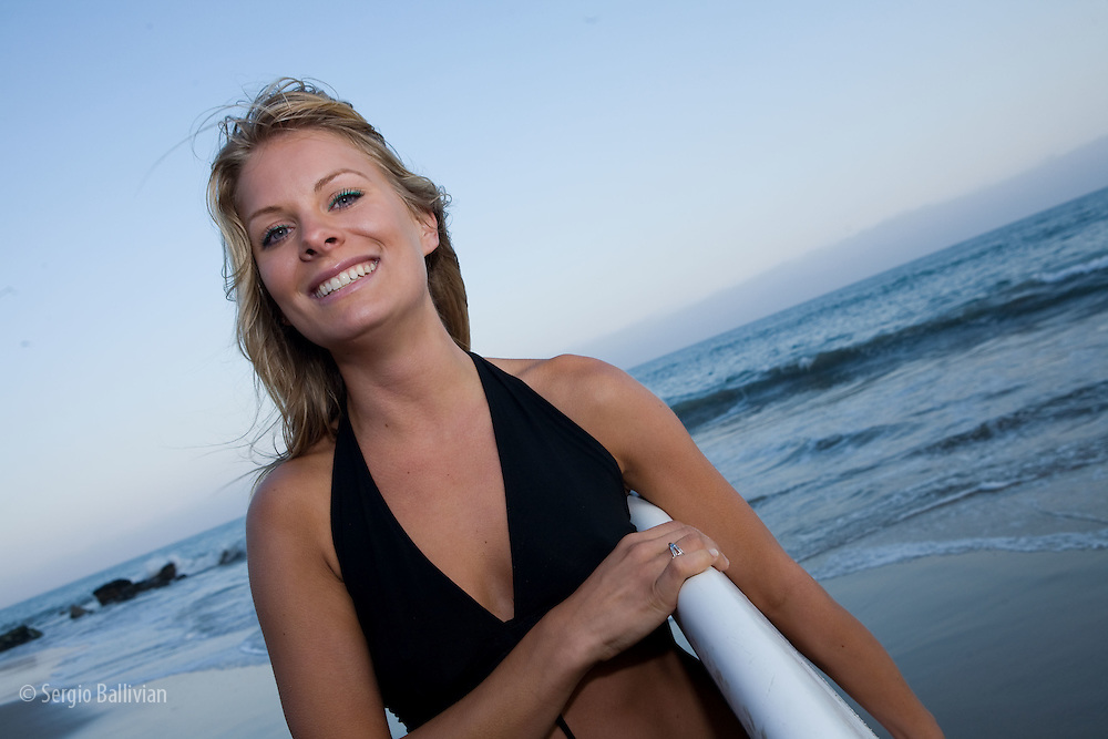 Lifestyle portrait of a young female surfer on  a beach in Malibu Beach, CA
