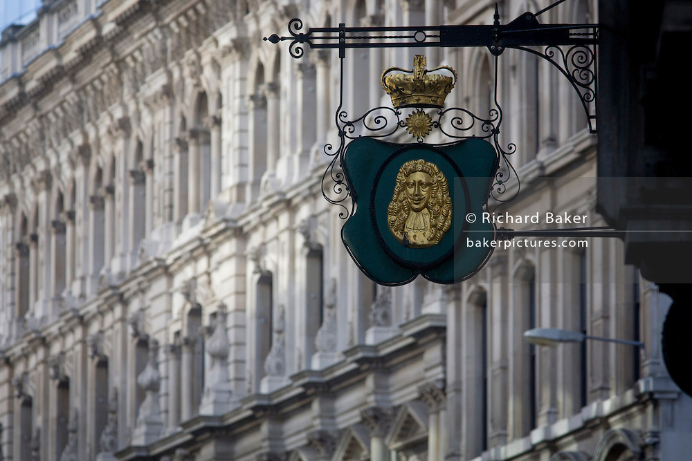 A detail of a City of London Goldsmith's street sign on the corner of Suffolk Lane and Lombard Street in the heart of the capital's financial district. A golden crown sits above the head of an eminent 18th century financier. Such hanging signs were banned by Charles II, but replicas were erected for the coronation of Edward VII in 1902.