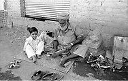 Pakistan 1986 .Darra Adamkhel is Pakistan's largest weapons bazaar and factory, renowned for its gun making expertise since the late 19th century, Darra is a sprawl of hundreds of workshops where some 3,500 gunsmiths toil on replica weapons..Grandfather whit his nephew builds the kick of a rifle.