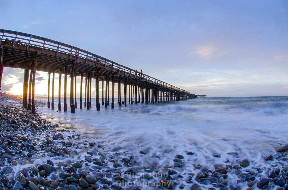 Wide-angle time exposure of a 6.36' king tide at sunrise washing waves and whitewater on the beach under the Ventura Pier in Ventura, California on December 22, 2015.