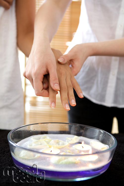 Woman receiving heat therapy on hand over bowl filled with candles