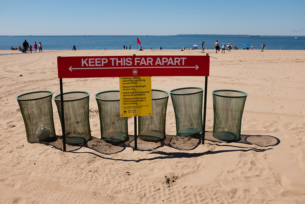 """Brooklyn, NY - 14 June 2020. A sign reading """"keep thsi far apart"""" and indicating 6 feet of social distance on the beach at Coney Island reminds people to keep well apart from each other. At this time the beach is still closed to swimming."""