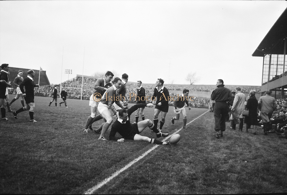 J Fortune, Irish right wing handles a New Zealander into touch,..Irish Rugby Football Union, Ireland v New Zealand, Tour Match, Landsdowne Road, Dublin, Ireland, Saturday 7th December, 1963,.7.12.1963, 12.7.1963,..Referee- H Keenen, Rugby Football Union, ..Score- Ireland 5 - 6 New Zealand, ..Irish Team, ..T J Kiernan, Wearing number 15 Irish jersey, Full Back, Cork Constitution Rugby Football Club, Cork, Ireland,..J Fortune, Wearing number 14 Irish jersey, Right Wing, Clontarf Rugby Football Club, Dublin, Ireland,..P J Casey, Wearing number 13 Irish jersey, Right Centre, University College Dublin Rugby Football Club, Dublin, Ireland, ..J C Walsh,  Wearing number 12 Irish jersey, Left Centre, University college Cork Football Club, Cork, Ireland,..A T A Duggan, Wearing number 11 Irish jersey, Left Wing, Landsdowne Rugby Football Club, Dublin, Ireland,..M A English, Wearing number 10 Irish jersey, Stand Off, Landsdowne Rugby Football Club, Dublin, Ireland, ..J C Kelly, Wearing number 9 Irish jersey, Captain of the Irish team, Scrum Half, University College Dublin Rugby Football Club, Dublin, Ireland,..P J Dwyer, Wearing number 1 Irish jersey, Forward, University College Dublin Rugby Football Club, Dublin, Ireland, ..A R Dawson, Wearing number 2 Irish jersey, Forward, Wanderers Rugby Football Club, Dublin, Ireland, ..R J McLoughlin, Wearing number 3 Irish jersey, Forward, Gosforth Rugby Football Club, Newcastle, England, ..W J McBride, Wearing number 4 Irish jersey, Forward, Ballymena Rugby Football Club, Antrim, Northern Ireland,..W A Mulcahy, Wearing number 5 Irish jersey, Forward, Bective Rangers Rugby Football Club, Dublin, Ireland,  ..E P McGuire, Wearing number 6 Irish jersey, Forward, University college Galway Football Club, Galway, Ireland,  ..P J A O' Sullivan, Wearing  Number 8 Irish jersey, Forward, Galwegians Rugby Football Club, Galway, Ireland,..N A Murphy, Wearing number 7 Irish jersey, Forward, Cork Constitution Rugby Football Club, Cork, Ireland,..New Z