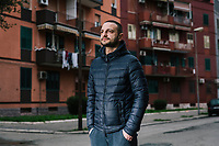 "TARANTO, ITALY - 22 FEBRUARY 2018: Luca Greco, an unemployed 30-years old living with his parents in Tamburi, the working-class district adjacent the ILVA steel mill, poses for a portrait, in Taranto, Italy, on February 22nd 2018.<br /> <br /> Luca Greco has worked occasionally in call centers for a minimum salary, but hasn't had a job since 2013. His 65 years-old father is unemployed  since 2003 and his mother works as a care-giver. He lives with his parents and 13 years-old brother. ""I  absolutely don't see a future in Taranto or in Italy. If I leave Tamburi, I will leave the country. I see a dark, tragic future"". When asked who he will vote in the upcoming Italian General Elections, Luca said: ""You could still make a distinction between the political parties in the 1960's. They're all the same. The Five Stars Movement is the new thing. One could vote them to give them a chance. But I won't"".<br /> <br /> Taranto, a  formerly lovely town on the Ionian Sea has for the last several decades been dominated by the ILVA steel mill, the largest steel plant in Europe. It was built by the government in the 1960s as a means of delivering jobs to the economically depressed south, but has been implicated for a cancer as dioxin and mercury have seeped into local groundwater, tainting the food supply, while poisoning the bay and its once-lucrative mussels."