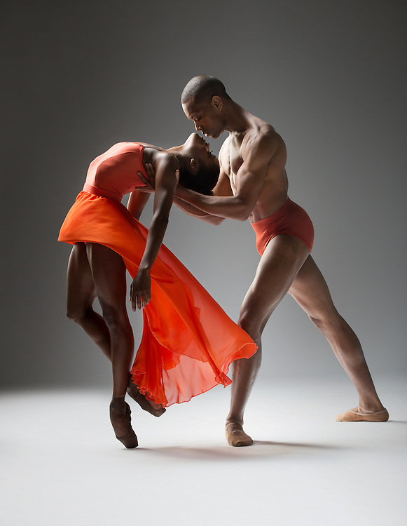 Pax de duex of two contemporary ballet dancers from Dance Theatre of Harlem with a red romantic tutu. Shot in the studio against a dark background. Photographed by dance photographer, Rachel Neville.