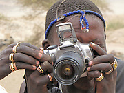 Portrait of a young Maasai tribesman with a camera. Maasai is an ethnic group of semi-nomadic people. Photographed in Tanzania
