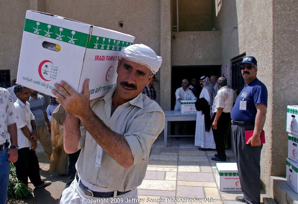 A man carries an emergency aid package for poor people of his community at the Community of Leaders and Chiefs for Iraqi Tribes in Baghdad, Iraq, Thursday, August 7, 2003. Each sheik, or chief of the their tribe, gets 15 boxes of aid for the poor. For many Iraqis, the community is the only place they can go to receive dependable aid. The community receives the aid packages from Saudi Arabia.