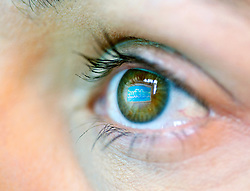 Detail of social networking website Twitter reflected in eye of a woman