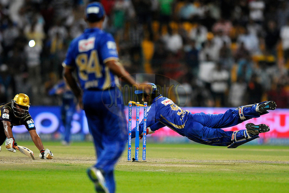 Sanju Samson of the Rajatshan Royals dives to take the bails off to get  Suryakumar Yadav of the Kolkata Knight Riders  run out during the super over during match 19 of the Pepsi Indian Premier League 2014 Season between The Kolkata Knight Riders and the Rajasthan Royals held at the Sheikh Zayed Stadium, Abu Dhabi, United Arab Emirates on the 29th April 2014<br /> <br /> Photo by Pal Pillai / IPL / SPORTZPICS