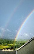 double rainbow over hilly woodland and farmland
