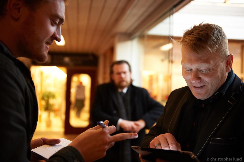 "Sven Becker interviewing the Mayor of Reykjavik Jón Gnarr at the offical opening of the website ""Better Reykjavik"" at Gerðuberg, Reykjavík. Better Reykjavík is a venue of cooperation for the inhabitants of Reykjavík. Jón Gnarr is showing Sven something on his iPad. Björn Blöndal, Jón's advisor in background."