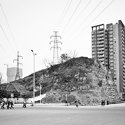 CHONGQING, CHINA - JAN 30, 2011: An electricity pole on the border of a street crossing in a brand new area in northern Chongqing. In the suburbs, where they build when the demolishing is yet not finished, it is common to find constrasting elements, incongruous pairings. Funny sometimes.