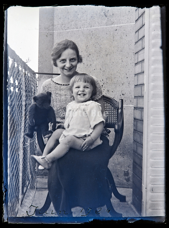 happy mother with smiling toddler and teddy bear sitting on the balcony France 1924