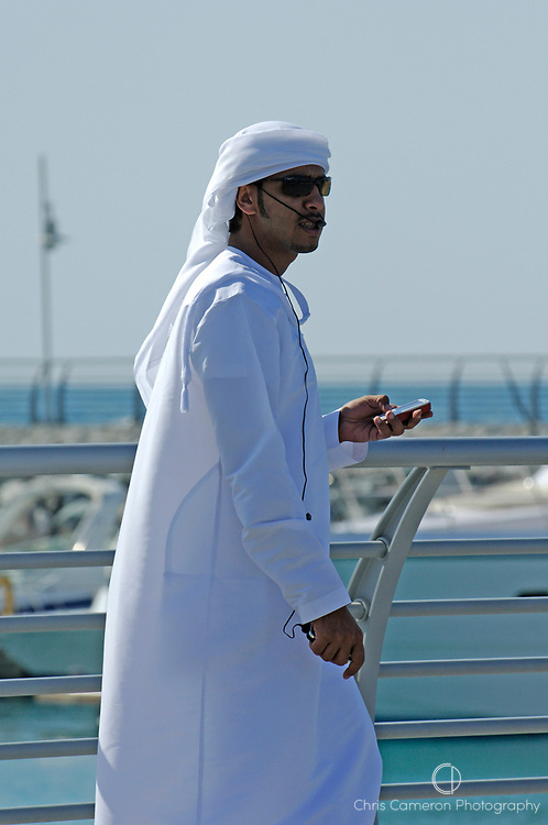An Arabic man talks on a cellular phone using a headset. Dubai, United Arab Emirates. 20/1/2007