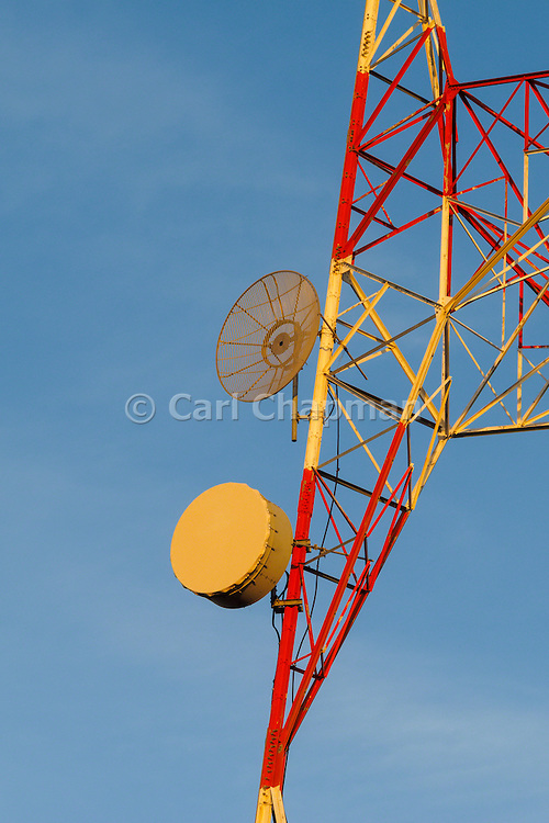 Microwave dish antenna on television broadcast transmission lattice tower at sunrise