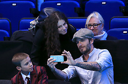 A fan gets a photograph taken with Romeo Beckham and David Beckham during day five of the Barclays ATP World Tour Finals at The O2, London.