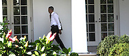 With his coat over his shoulder President Barack Obama walks on the Colonade of the White House to the Oval Office after returning to the White House from a Health Care event in Falls Church, VA. photo by Dennis Brack