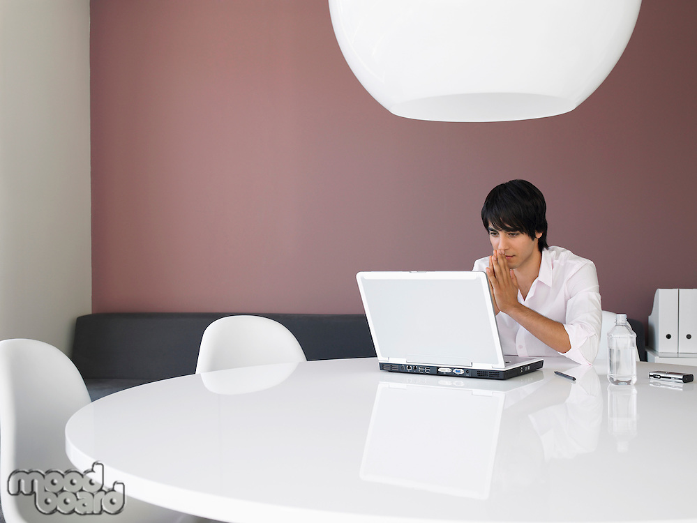 Asian businessman using white laptop in contemporary office space
