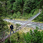Jamie O'Donnell crosses a wire foot bridge while trecking through the Lewis Pass area, South Island, New Zealand. Photo by Jen Klewitz