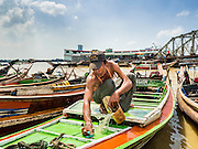 22 OCTOBER 2015 - YANGON, MYANMAR: A man who operates a cross river ferry in Yangon cleans the deck of his boat on the Yangon side of the river.     PHOTO BY JACK KURTZ
