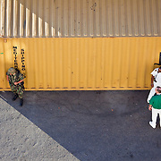 Two Men from the Cruise Crew talk while a Guard take cover in the shade at the Mazatlan Port in Mexico