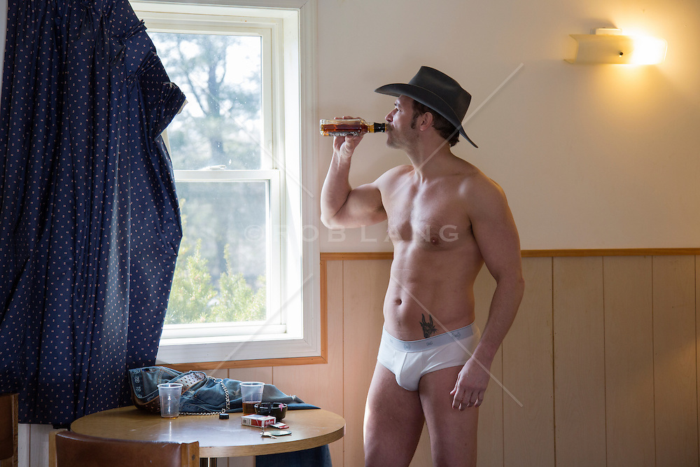 cowboy wearing only his hat and underwear in a sleazy motel room drinking from a bottle of Jack Daniels while he looks out the window