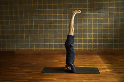 Mature Man Practicing Yoga, Headstand