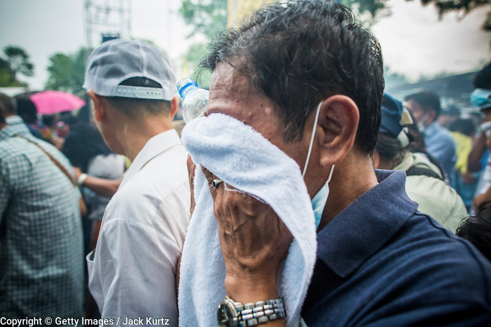 24 NOVEMBER 2012 - BANGKOK, THAILAND:   People try to get away from tear gas used by Thai riot police during a large anti government, pro-monarchy, protest  on November 24, 2012 in Bangkok, Thailand. The Siam Pitak group, which sponsored the protest, cited alleged government corruption and anti-monarchist elements within the ruling party as grounds for the protest. Police used tear gas and baton charges againt protesters.       PHOTO BY JACK KURTZ