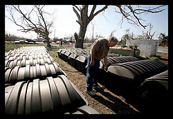16th Feb, 2006. Devastated Plaquemines Parish, just south of New Orleans, Louisiana. Coffins, sealed in hard plastic storage bins await re-burial at the Turner cemetery. Council man and local contractor Mike Mudge checks tags in the cemetery, surrounded by just a few of the hundreds of coffins he has recovered from all over the parish. The cemeteries in the parish were devastated by hurricane Katrina. Many of the coffins floated away and have now been recovered from the marshes and surrounding areas. Most of the remains have been identified and await burial for the second time. For now though, they wait above ground in cemeteries awaiting tombs tied to the land.