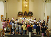 FINAL SCHOOL MASS -- Students and staff from St. Louis Catholic Academy in Caledonia, Wis., gather around the altar with Fr. Mark Danczyk at St. Louis Church to pray the Our Father during a final school Mass June 9. A dwindling enrollment forced the Catholic school to close its doors this spring. The school's K-8 enrollment was 44 this year, with some grades having as few as three students. (Photo by Sam Lucero)