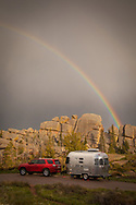 A rainbow arcs over an Airstream travel trailer parked at a campsite near a rock formation in Vedauwoo, near Laramie, WY.