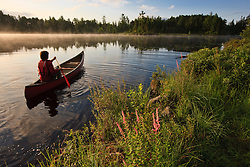 A man canoeing on Little Bear Brook Pond in Errol, New Hampshire. Northern Forest