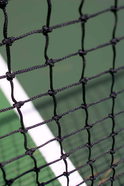 looking through a tennis net at the line and green court.