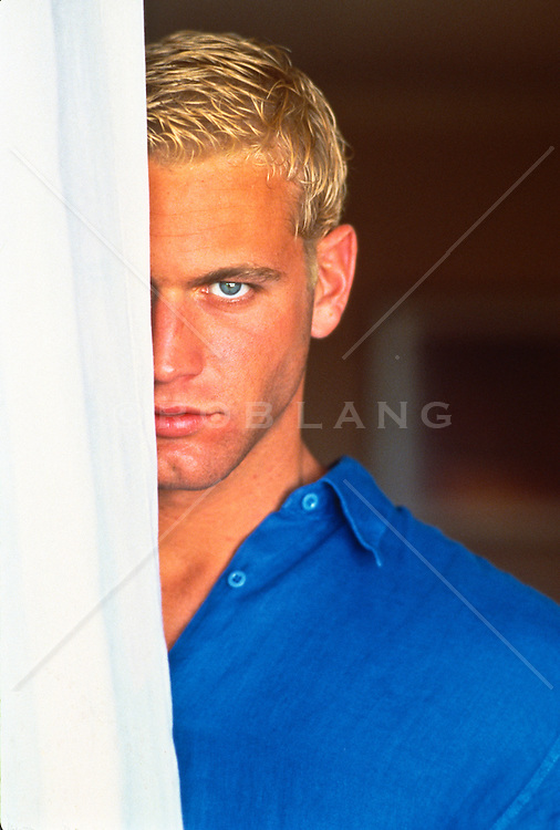 Good looking blond haired man hiding half his face behind a curtain