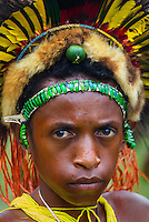Young boy dressed as a traditional tribal warrior witha crown of colourful parrot's feathers and animal skins at the Goroka show in Papua New Guinea.He is also wearing a head lace made from the iridescent green wing casings of beetles.