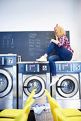 May 24, 2017 - Female laundrette owner sitting on top of washing machine writing on chalkboard (Credit Image: © Image Source via ZUMA Press)