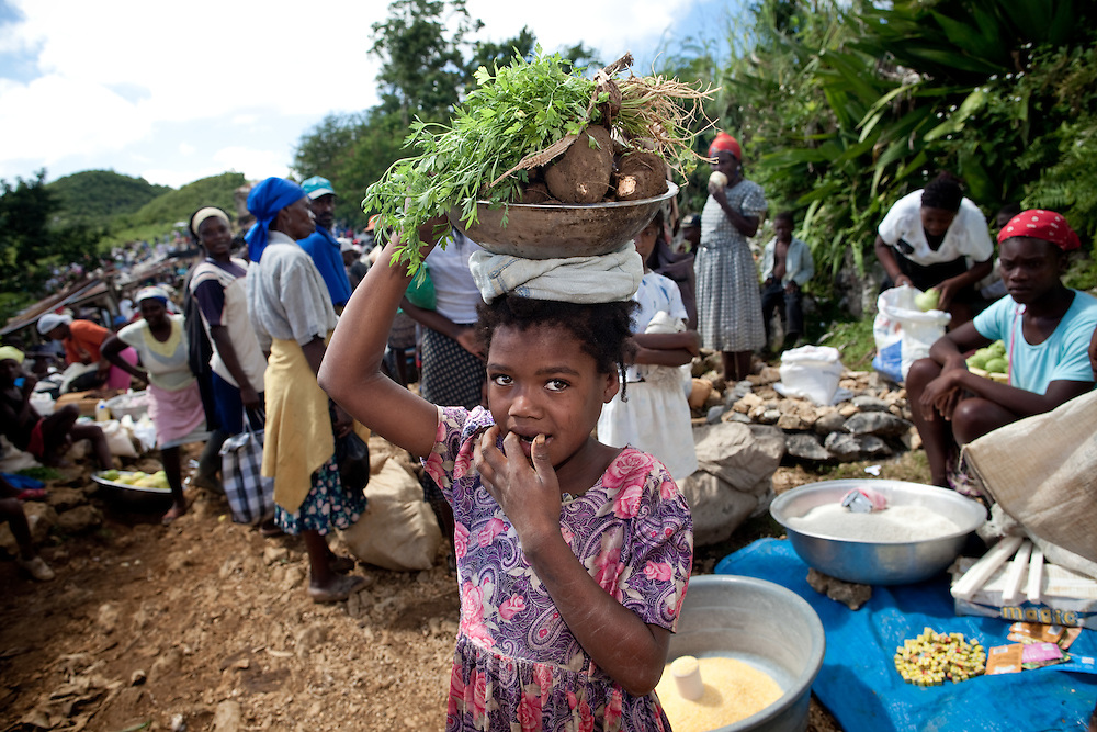 A girl carries yams on her head at a market near Caye Michel in the Massif de la Hotte, Haiti