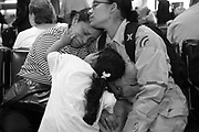 Awilda Vasquez comforts her mother and daughter as her flight is called for boarding. Emily tries to make her grandmother smile by pulling her lips with her finger.  Awilda is returning to Iraq as a member of the National Guard 50th Main Support Battalion.