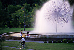 Stock photo of people sitting at the Gus Wortham Fountain at dusk