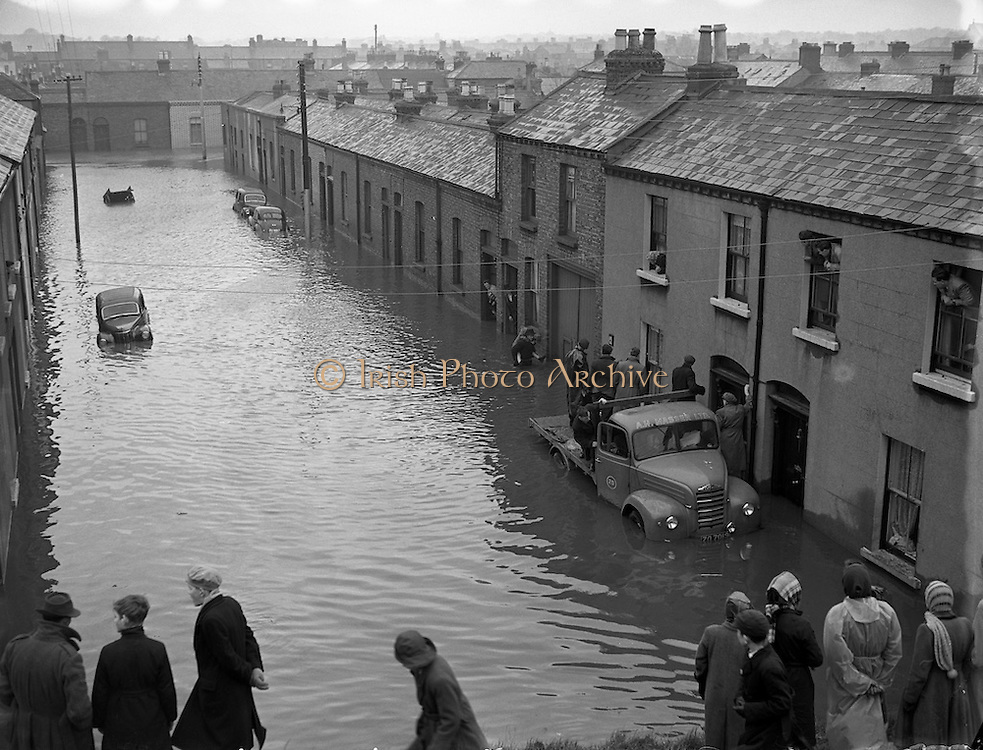 People gather by doors and window along flooded streets just off of North Strand Street between the 8th-12th of December 1954.
