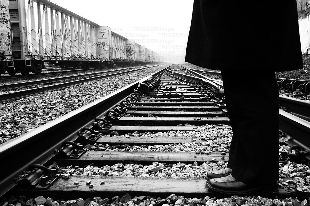 A man wearing dark trousers and coat standing on a railway line