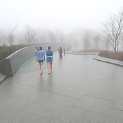 A pair of runners brave the weather at the Martin Luther King Memorial on the banks of the Tidal Basin in Washington DC on a cold, misty winter's morning.