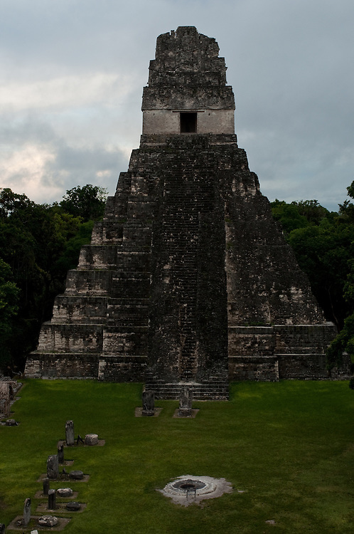 Dusk falls on the Great Plaza at Tikal National Park, in the Petén Basin in Northern Guatemala, and bathes the limestone slabs of the Temple of the Jaguar Priest, also known as Temple I, in soft light evening light.