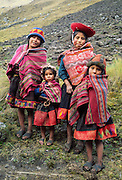 Four Andean mountain children dress in traditional red ponchos in the Cordillera Urubamba, Andes highlands, Peru, South America. The moderately strenuous trek from Lares to Patacancha (near Ollantaytambo) traverses rugged, little-visited country in the Cordillera Urubamba across passes at 13,800 and 14,200 feet elevation. A five hour bus ride from Cuzco reaches Lares, where you can soak in developed hot spring pools. Llamas and horses carried our loads for two nights of camping at 12,500 feet elevation.