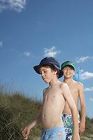 Two boys (6-11) walking in sand dunes