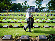"11 NOVEMBER 2018 - KANCHANABURI, KANCHANABURI, THAILAND: A man walks through Kanchanaburi War Cemetery  during the Rememberance Day ceremony in Kanchanaburi, Thailand. Kanchanaburi is the location of the infamous ""Bridge On the River Kwai"" and was known for the ""Death Railway"" built by Japan during World War II using allied, principally British, Australian and Dutch, prisoners of war as slave labor. There are 6,982 people buried in the cemetery, including 5,000 Commonwealth soldiers and 1,800 Dutch soldiers. November 11, 2018 marked the 100th anniversary of the end of World War I, celebrated as Rememberance Day in the UK and the Commonwealth and Veterans' Day in the US.   PHOTO BY JACK KURTZ"