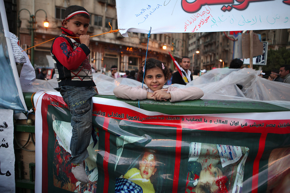 Children play near posters of some of the more than 300 people killed by Mubarak's forces during protests calling for his ouster.