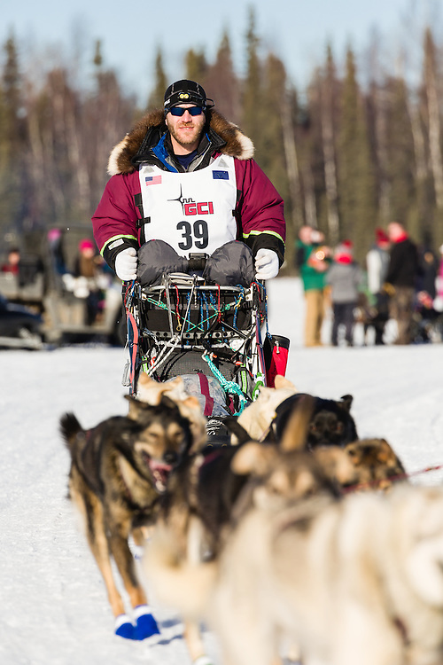 Musher Noah Burmeister competing in the 44th Iditarod Trail Sled Dog Race on Long Lake after leaving the restart on Willow Lake in Southcentral Alaska.  Afternoon. Winter.