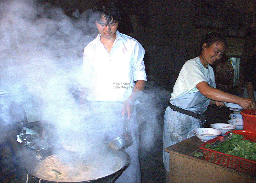 Steaming noodles being prepared for the evening dinner at a roadside cafe.