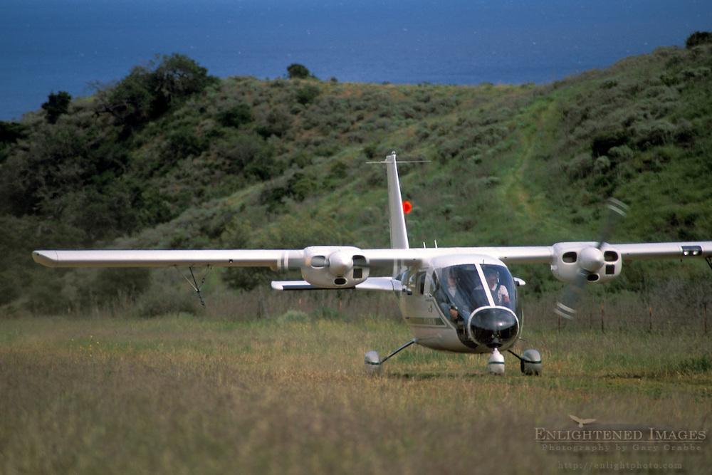 Twin engine airplane taking off from rural grass landing strip in hills of Santa Cruz Island, Channel Islands, California